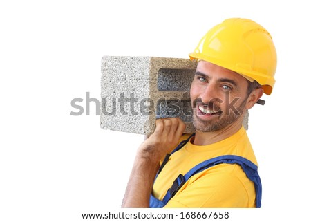Confident handsome young builder or bricklayer wearing a safety helmet carrying a cement block on his shoulder and looking at the camera with a friendly smile, isolated on white
