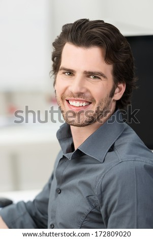 Confident handsome young businessman with a lovely friendly smile working in his office, closeup facial portrait - stock photo