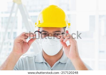Confident handyman wearing protective eyewear at construction site - stock photo
