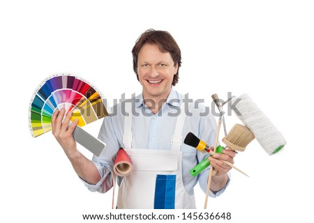 Confident handyman with samples displaying color charts for paint while holding a roll of wallpaper and his tools in his hands - stock photo