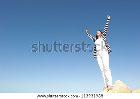 Confident, happy, successful and attractive mature, senior woman on top of rock, mountain, isolated with blue sky as background and copy space. - stock photo
