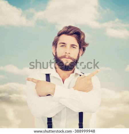 Confident hipster pointing sideways with arms crossed against beautiful blue cloudy sky - stock photo