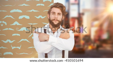 Confident hipster pointing sideways with arms crossed against composite image of mustaches - stock photo