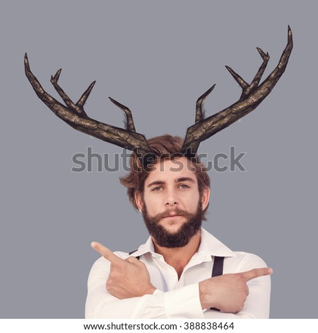 Confident hipster pointing sideways with arms crossed against grey - stock photo