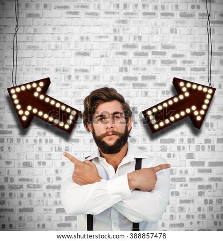 Confident hipster pointing sideways with arms crossed against grey brick wall - stock photo
