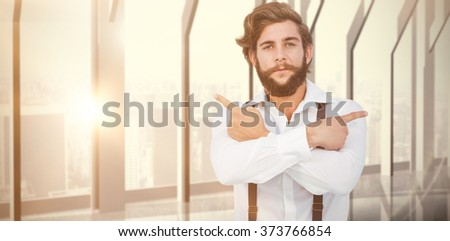 Confident hipster pointing sideways with arms crossed against room with large window looking on city - stock photo