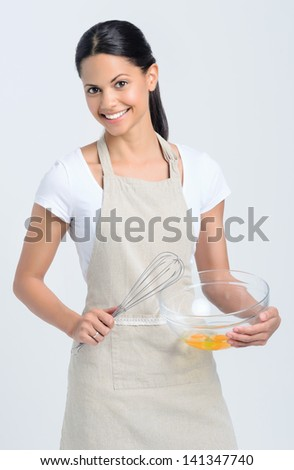 Confident homemaker chef with whisk and glass bowl of eggs, ready to cook and bake - stock photo