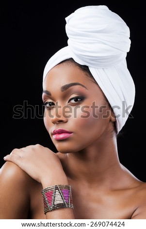 Confident in her beauty. Beautiful African woman wearing a headscarf and touching her shoulder while standing against black background - stock photo
