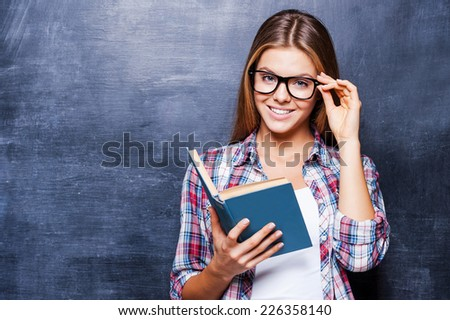 Confident in her knowledge. Cheerful young women holding book and smiling while standing against blackboard - stock photo