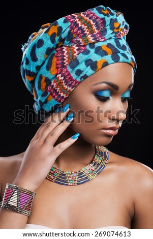 Confident in her perfect look. Beautiful African woman wearing a headscarf and necklace looking away and touching her face while standing against black background