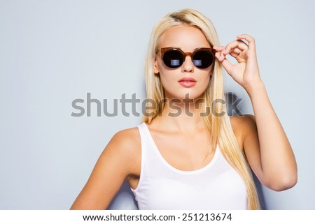 Confident in her style. Beautiful young blond hair women adjusting her sunglasses while standing against grey background