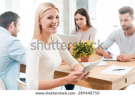 Confident in her team. Beautiful young blond hair woman holing digital tablet and smiling while sitting together with her colleagues at the desk in office  - stock photo