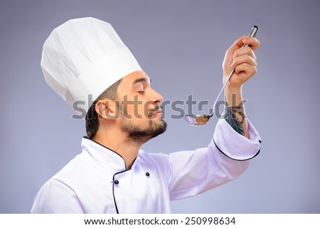 Confident in his culinary craft. Side view portrait of handsome cook holding a soup ladle and smelling it with his eyes closed while standing over grey background with copy space - stock photo