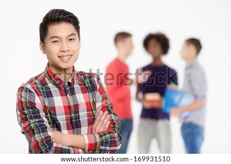 Confident in his friends. Cheerful Chinese teenage boy keeping arms crossed and smiling while his friends standing on background - stock photo
