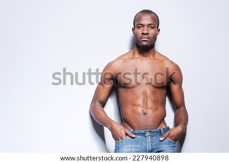 Confident in his perfect body. Handsome young shirtless African man looking at camera and holding hands in pockets while leaning at the grey wall - stock photo