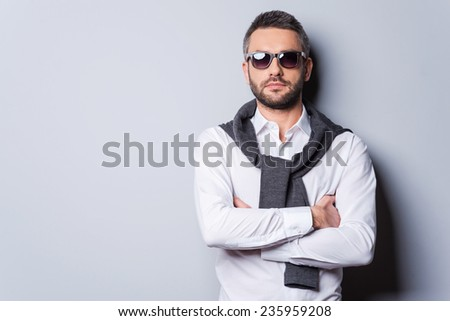 Confident in his perfect look. Handsome young man in sunglasses and smart casual wear keeping arms crossed while standing against grey background - stock photo
