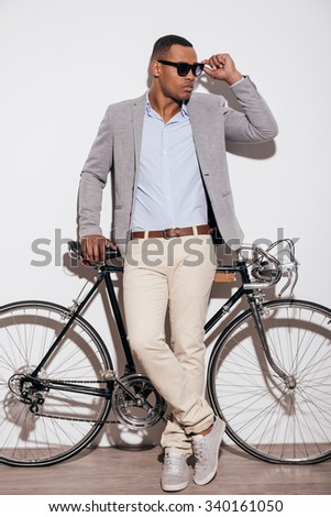 Confident in his perfect style. Full length of confident young African man adjusting his sunglasses and leaning at his retro styled bicycle while standing against white background - stock photo