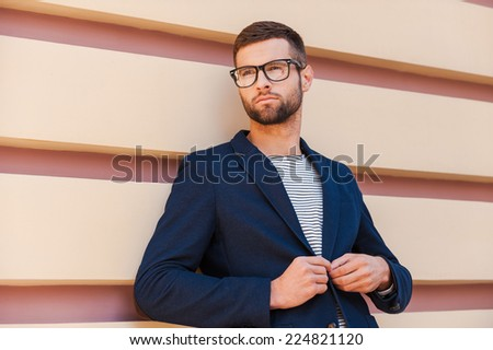 Confident in his perfect style. Handsome young man adjusting his jacket while leaning at the striped wall - stock photo