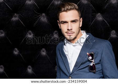 Confident in his perfect style. Handsome young man in smart casual wear holding hands in pockets and looking at camera while standing against black background  - stock photo