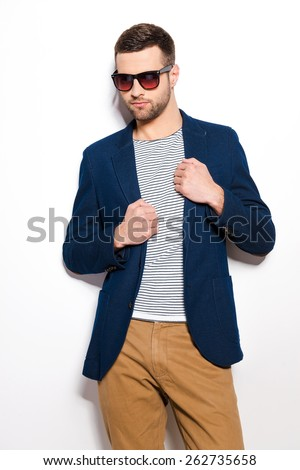 Confident in his perfect style. Handsome young man in sunglasses adjusting his jacket while standing against white background  - stock photo