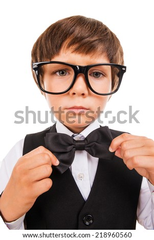 Confident in his skills. Cute little boy adjusting his bow tie and looking at camera while standing isolated on white - stock photo