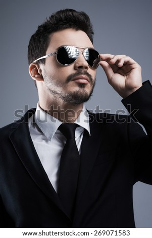 Confident in his style. Handsome young man in formalwear adjusting his sunglasses and looking away while standing against grey background