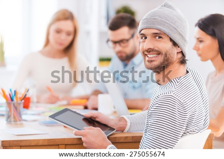 Confident in his team. Handsome young man looking over shoulder and smiling while holding digital tablet and sitting together with his colleagues at the wooden table in office - stock photo
