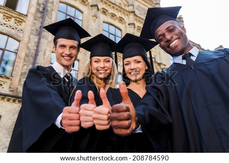Confident in their successful future. Low angle view of four college graduates in graduation gowns standing close to each other and showing their thumbs up - stock photo