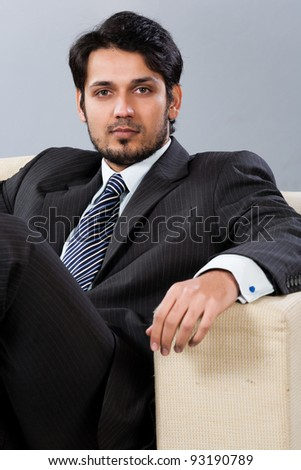 confident Indian businessman sitting on sofa - stock photo