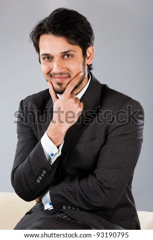 confident Indian businessman sitting on sofa
