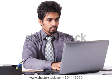 confident Indian businessman working on the laptop isolated on white - stock photo