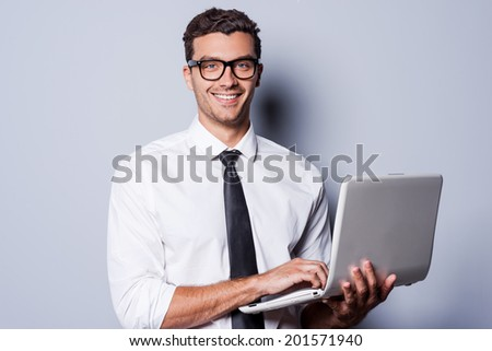 Confident IT expert. Handsome young man in shirt and tie working on laptop and smiling while standing against grey background - stock photo