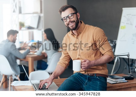 Confident IT professional. Confident young man working on laptop and smiling while his colleagues talking in the background - stock photo