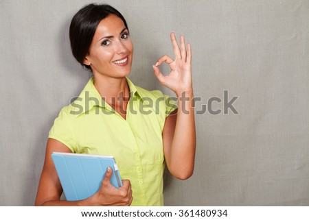 Confident lady showing ok sign while holding tablet in green blouse and hair back and smiling with a toothy smile while looking at camera on grey texture background - stock photo