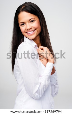 Confident latino woman smiling and happy in casual clothing isolated on grey background - stock photo