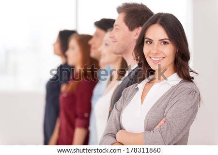 Confident leader. Attractive young woman holding arms crossed and smiling while group of people standing behind her in a row - stock photo