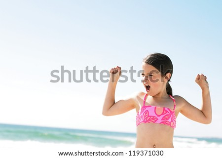 Confident little girl showing her muscles while playing at the beach - stock photo