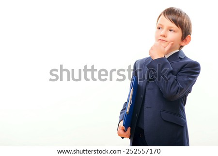 Confident little leader. Thoughtful little boy in formalwear holding a blue clipboard and touching his chin while standing isolated on white background with copy space - stock photo