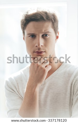 Confident look. Confident young man holding hand on chin and looking at camera while standing against window - stock photo
