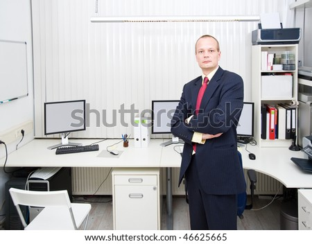 Confident looking business man, posing in front of a well equipped office, representing a small business owner - stock photo