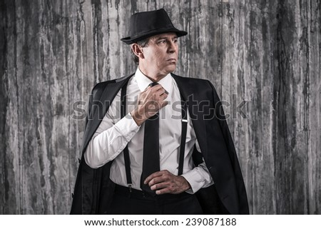 Confident mafia boss. Bossy senior man in gangster clothing adjusting his necktie and looking away while standing against a wall - stock photo
