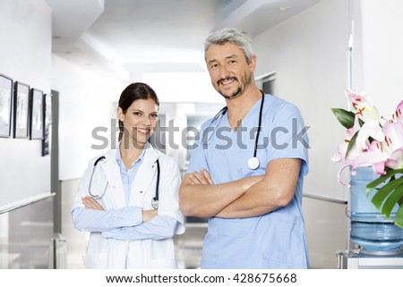 Confident Male And Female Physiotherapists Standing Arms Crossed - stock photo