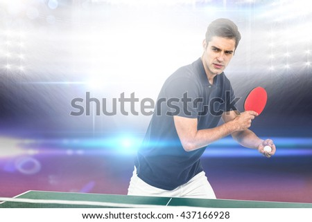 Confident male athlete playing table tennis against american football arena - stock photo