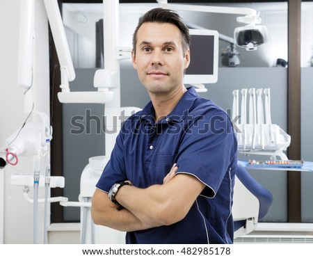 Confident Male Dentist With Arms Crossed At Clinic
