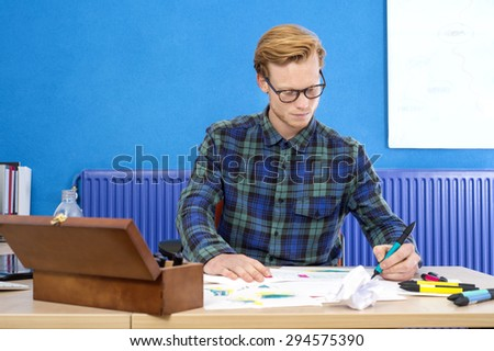 Confident male designer making sketch on paper at desk in creative office - stock photo
