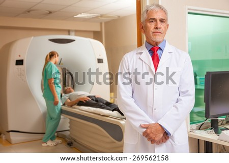 Confident male doctor in hospital with patient undergoing mri. - stock photo