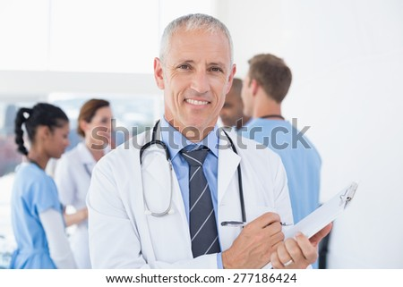 Confident male doctor smiling at camera in medical office - stock photo