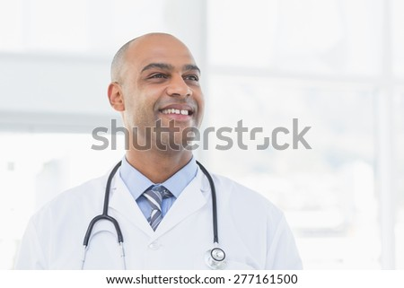 Confident male doctor smiling in medical office