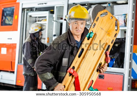 Confident male firefighter holding wooden stretcher against truck at fire station - stock photo