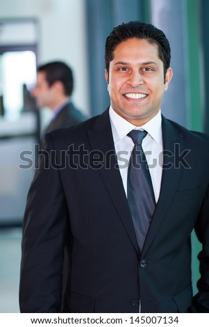 confident male indian business executive in modern office - stock photo